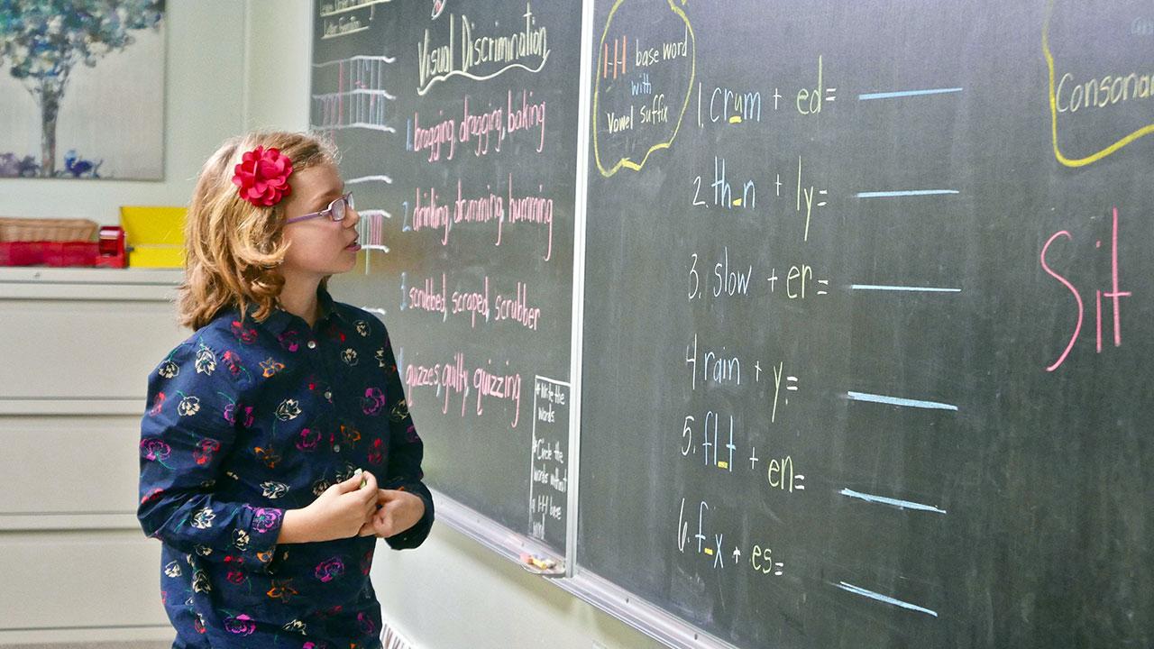 Lewis School student at blackboard